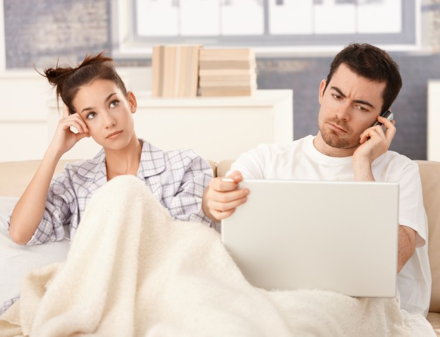 young-couple-in-bed-man-working-woman-bored
