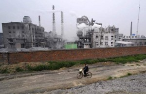 A man rides a bicycle past a chemical factory in Xiangfan,