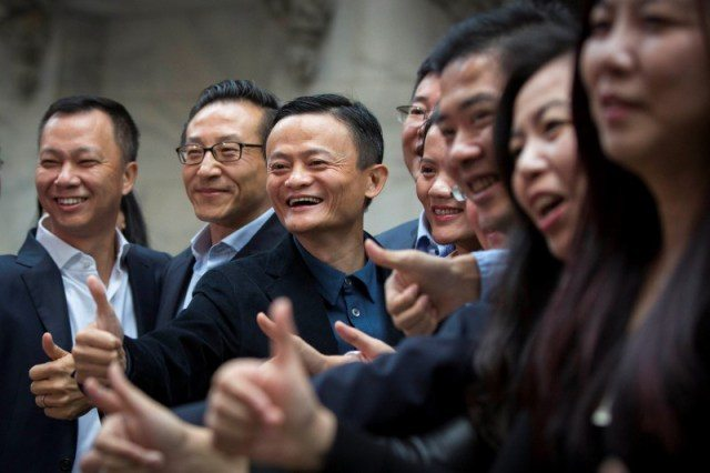 "Alibaba Group Holding Ltd founder Jack Ma gestures in front of the New York Stock Exchange before his company's initial public offering (IPO) under the ticker ""BABA"" in New York"