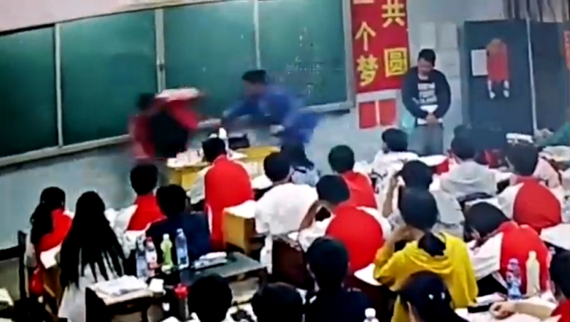 A middle school teacher in southern China has been suspended after assaulting two male students in front of the class.